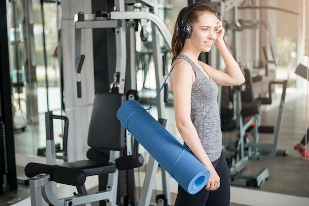 かなり若いスポーツ女性はジム、健康的なライフスタイルでマット付きのトレーニングです。