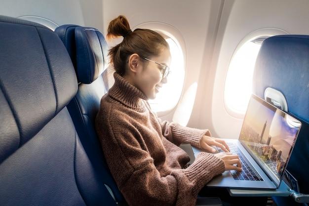 美しいアジアの女性は飛行機の中でラップトップで働いています。