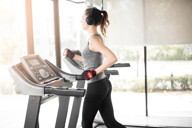かなり若いスポーツ女性がジムで健康的なライフスタイルのトレッドミルで実行されています。