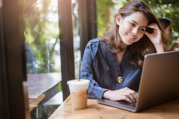 スマートビジネス女性はコンピューターで働いています。