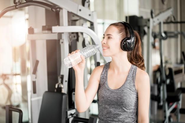 かなり若いスポーツ女性はジムで水を飲む