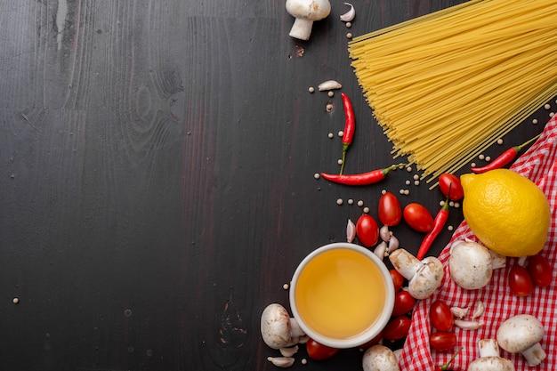 黒い木製の机の上のスパゲッティ食材。