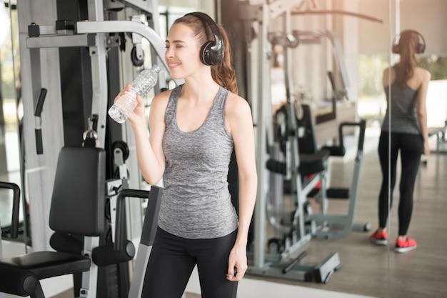 かなり若いスポーツ女性はジム、健康的なライフスタイルで水を飲む