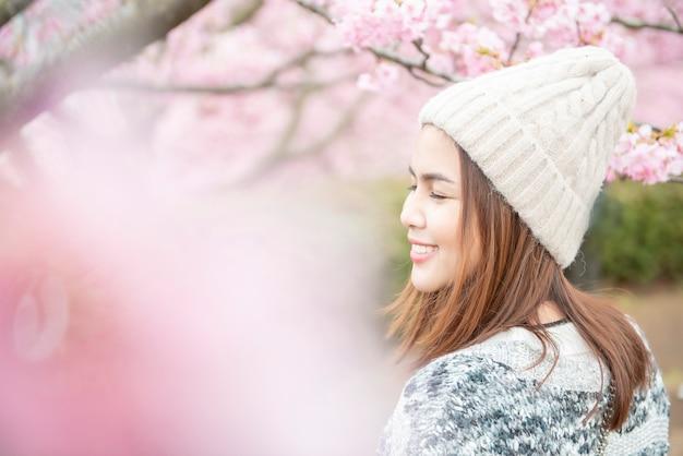 魅力的な女性は日本の松田で桜を楽しんでいます