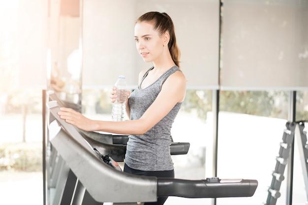 かなり若いスポーツ女性はジムで健康的なライフスタイルのトレッドミルで水を飲む