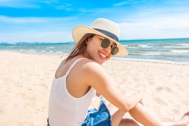 美しい女性はビーチに座っています。