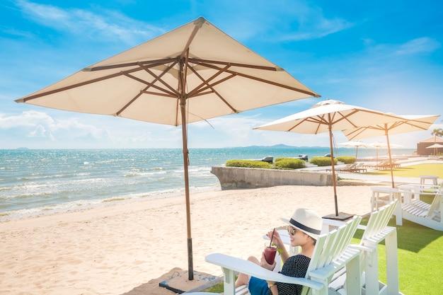 美しい女性はビーチで、傘の下でリラックス