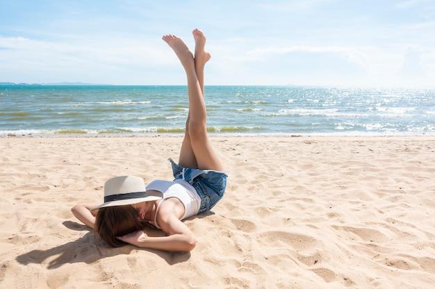 女性がビーチに横たわっています。