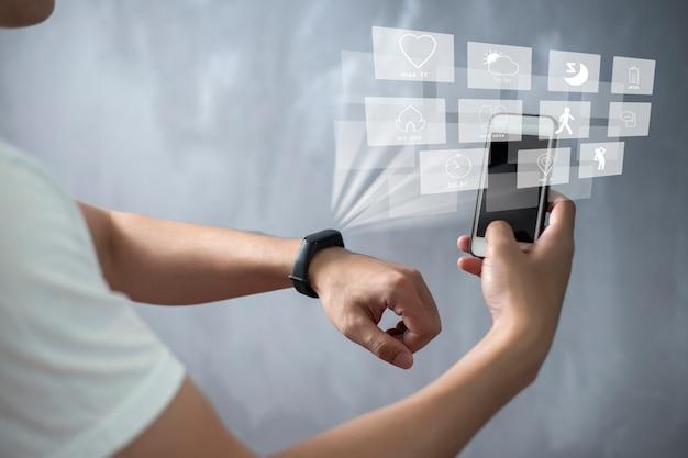 スポーツマンが仮想スクリーンデバイスでスマートバンドを使用しています