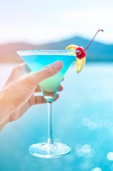 人間の手はビーチで夏の飲み物を保持しています。