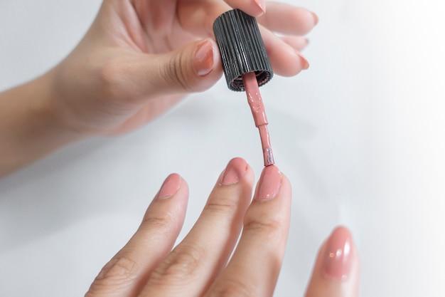 女性の指のクローズアップはマニキュアをしています。