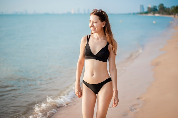 黒ビキニで美しい女性がビーチを歩いています