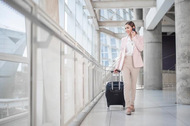 美しいビジネス女性は空港、ビジネス旅行の概念を歩いています。
