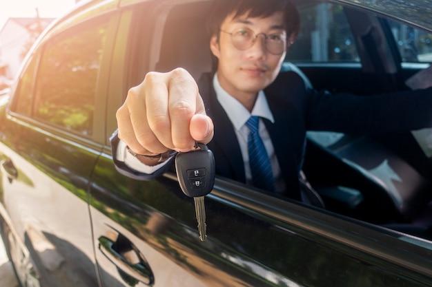 ビジネスの男性は車の中でキーの車を持っています。