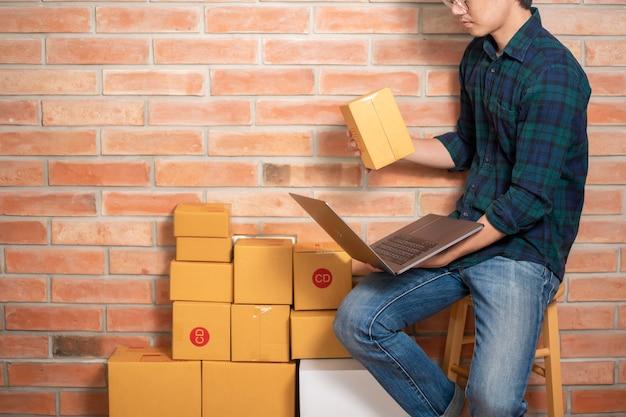 Человек-предприниматель владелец малого и среднего бизнеса упаковывает коробку, чтобы отправить своего клиента