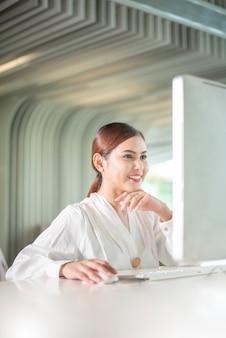 美しいビジネス女性は彼女のコンピューターで働いています。