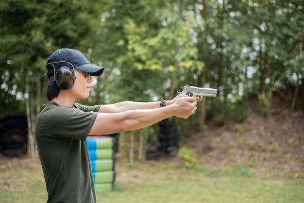 Мужчина практикует стрелять из пистолета