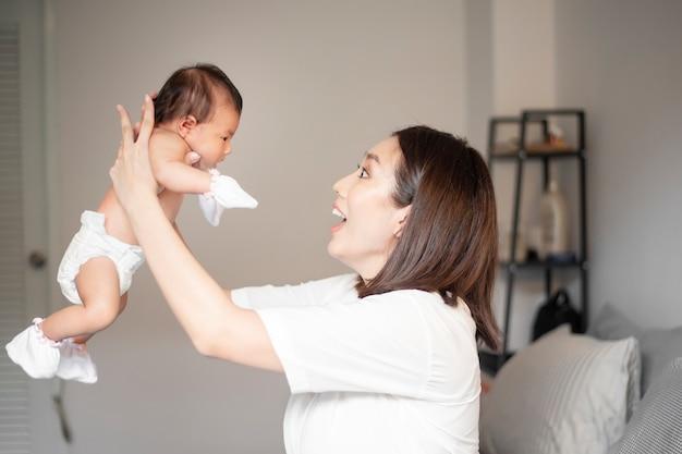 Красивая мама играет со своим новорожденным ребенком в спальне.