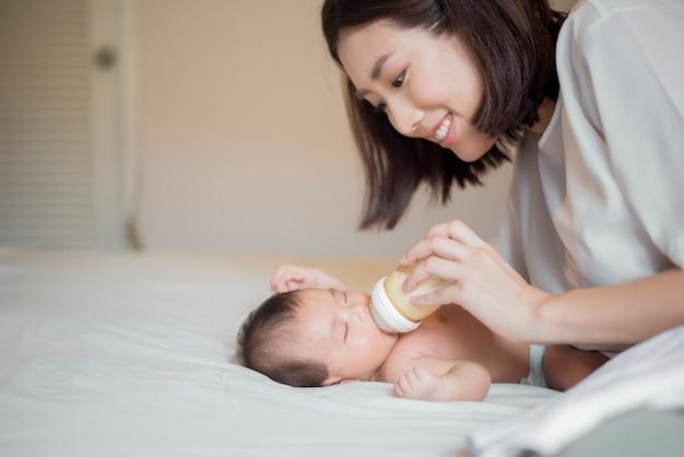 生まれたばかりの赤ちゃんの女の子は彼女の母親によって牛乳を飲んでいます。