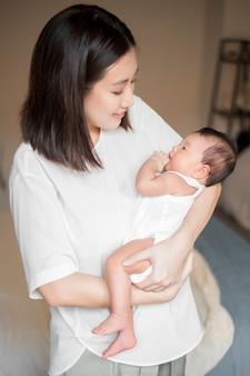 彼女の腕の中で生まれたばかりの赤ちゃんを持つ美しい女性