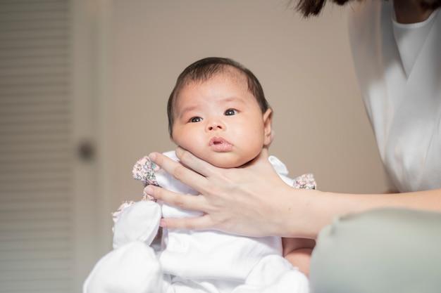 生まれたばかりの赤ちゃんの女の子は、牛乳を飲んだ後ママによって彼女の背中に触れて