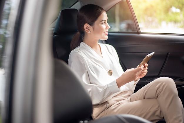 美しいビジネス女性は車で働いています。