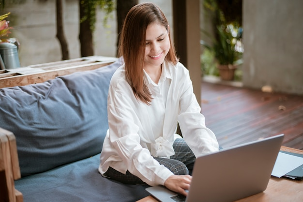 美しいビジネス女性はコーヒーショップで彼女のラップトップコンピューターで働いています。