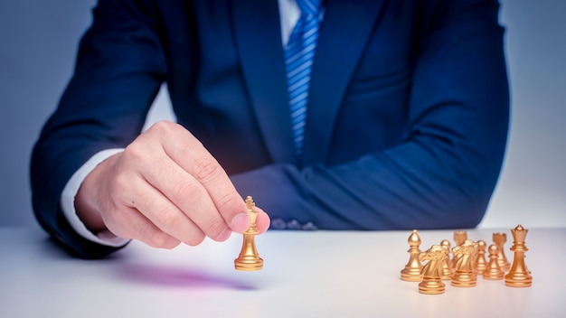 ビジネスの男性はチェス、経営戦略の概念を果たしています。