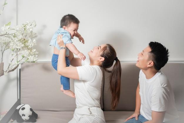 幸せなアジア家族は家で息子と一緒に楽しんでいます