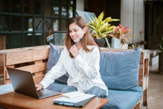 美しいビジネスの女性はコーヒーショップで彼女のラップトップコンピューターで働いています。