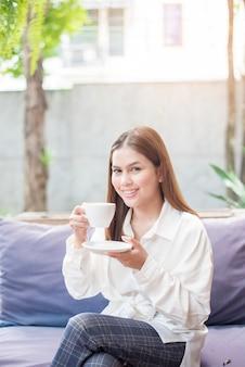 アジアビジネスの女性は、朝のコーヒーショップでコーヒーを飲んでいます。