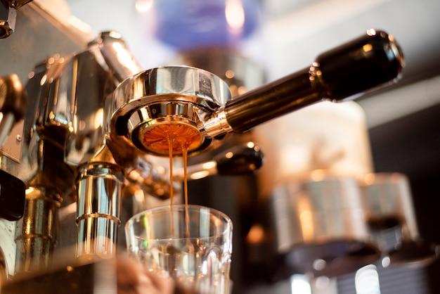 コーヒーマシンのクローズアップは、コーヒーショップでコーヒーを準備しています