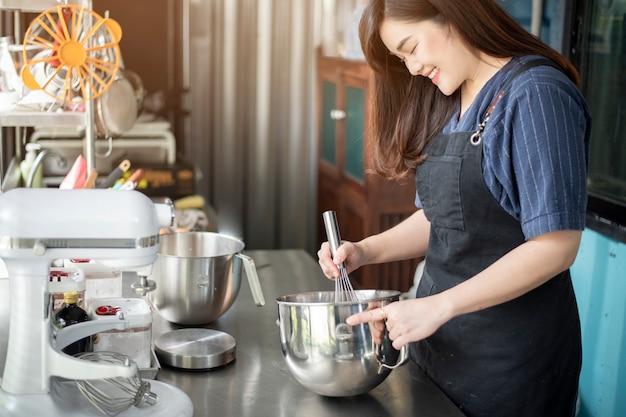 美しい女性はベーカリーを作っています