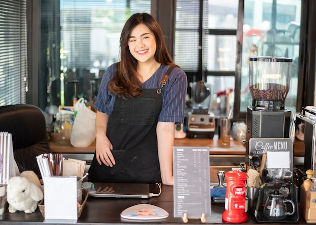 美しいバリスタは彼女のコーヒーショップで笑っています。
