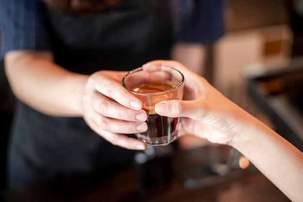 女性の手のクローズアップは、バリスタからホットコーヒーを取っています。