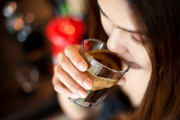 美しいアジアの女性はコーヒーを飲んでいます。