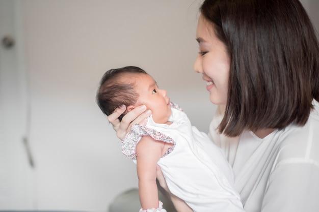 彼女の腕で生まれたばかりの赤ちゃんを保持している美しい女性
