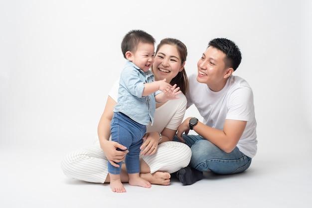 幸せなアジアの家族はスタジオで息子と一緒に楽しんでいます