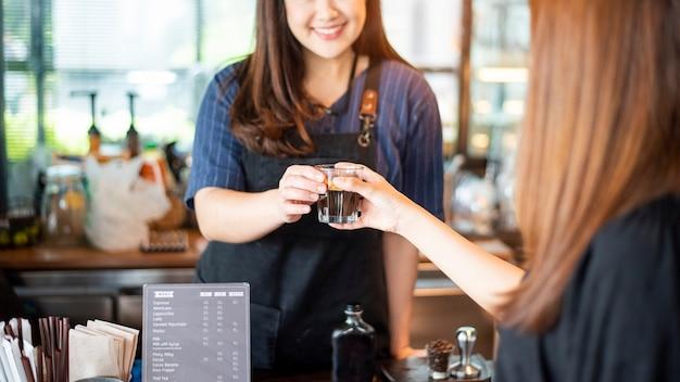 Крупным планом женская рука принимает горячий кофе из бариста
