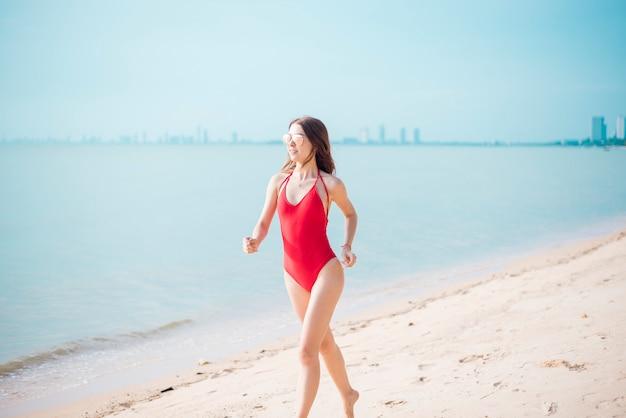 赤い水着の美しい白人女性がビーチで走っています