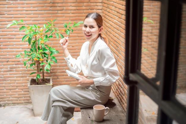 美しい女性は裏庭で働いています