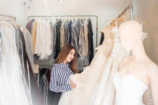 美しい女性はウェディングショップでウェディングドレスを探しています