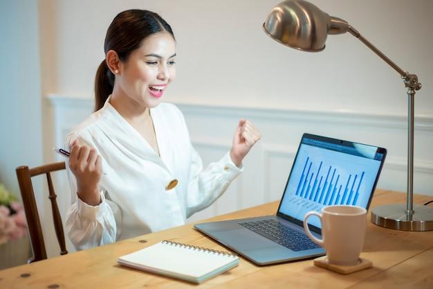 ビジネスの女性は彼女のオフィスの机で働いています。