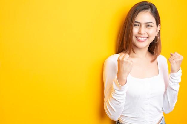 美しい大学生は黄色に笑っています。