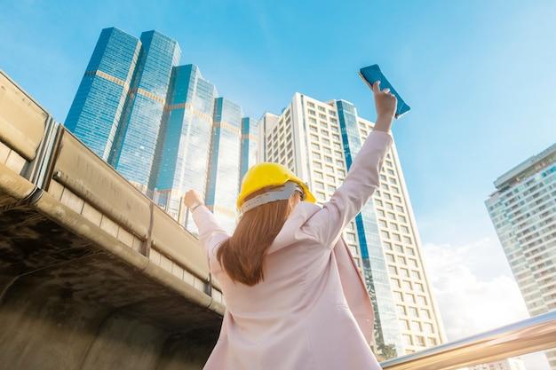 エンジニアリングの女性は屋外の街で働いています。