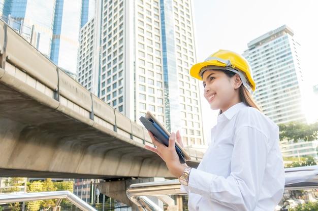 エンジニアリングの女性は、屋外の街背景で働いています。