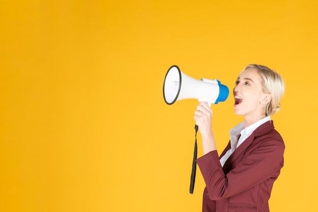 Деловая женщина объявляет от мегафона на желтом фоне