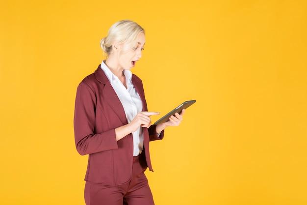 Бизнес-леди удивительно в студии желтый фон