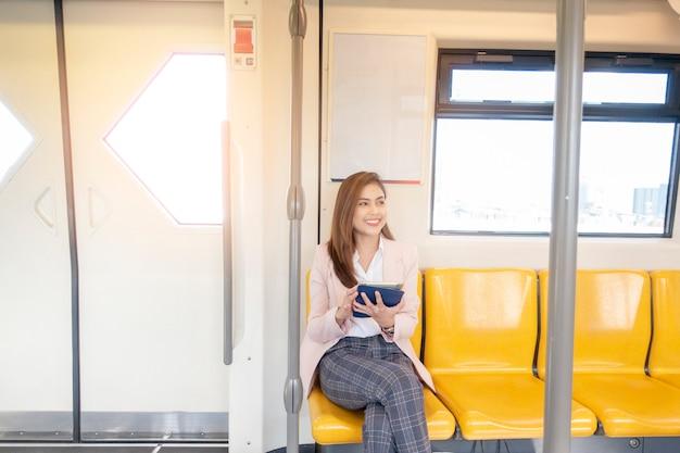 ビジネスの女性は地下鉄で働いています