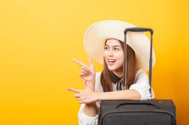 Красивая женщина путешественника возбуждает на желтом фоне